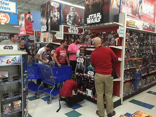 Hombres en el área de juguetería viendo juguetes de star wars