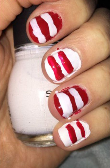 Chica con las uñas pintadas en blanco y rojo con las lineas raras