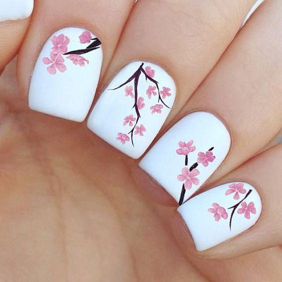 Chica con unas uñas blancas con flores de cerezo pintadas