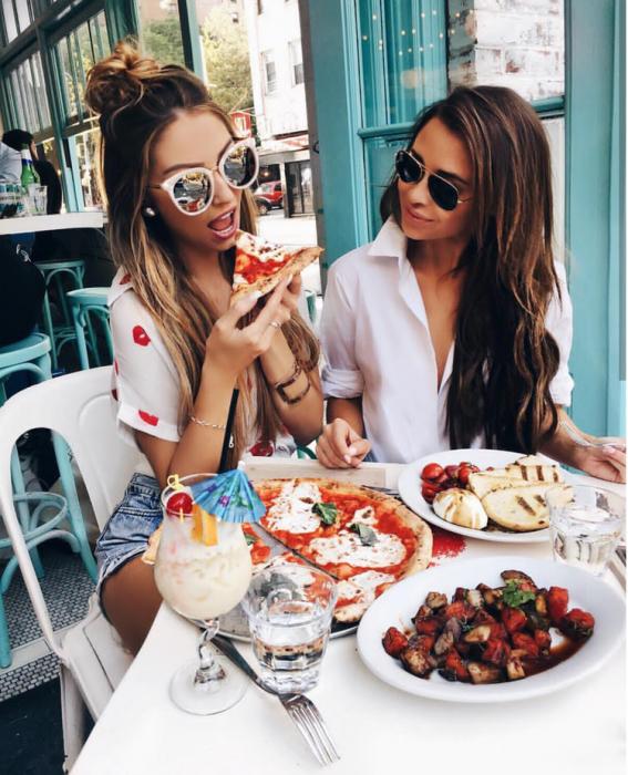 chicas desayunando pizza en un restaurante