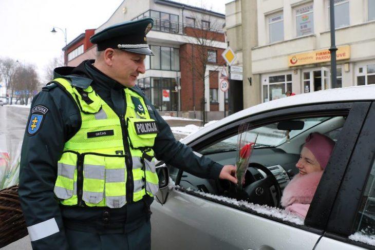 Policia regalando flores a una mujer