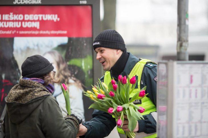 Policía entregando flores a las contudtoras