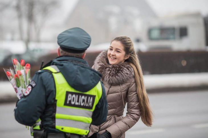 Policía entregándole una flor a una chica