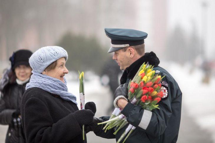 Policía regalando tulipanes rojos