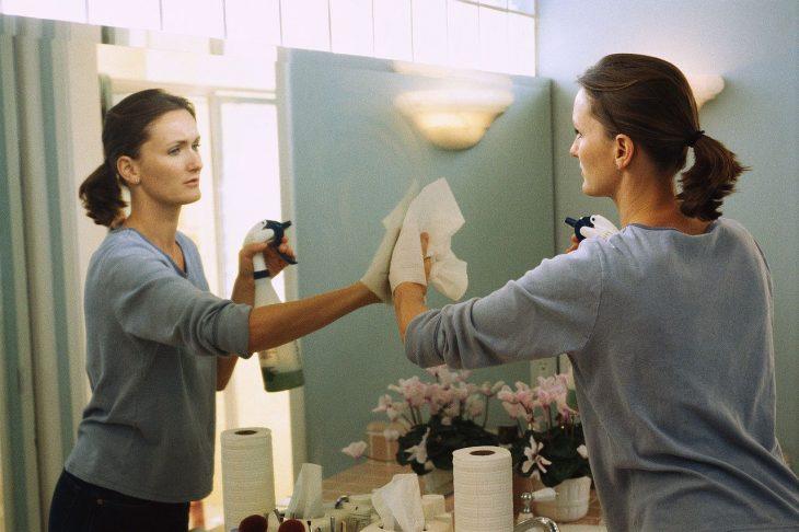 Mujer limpiando el vidrio de su baño con aerosol