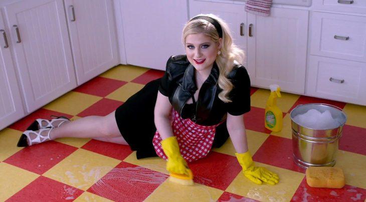 Chica sentada en el suelo limpiando con un cepillo