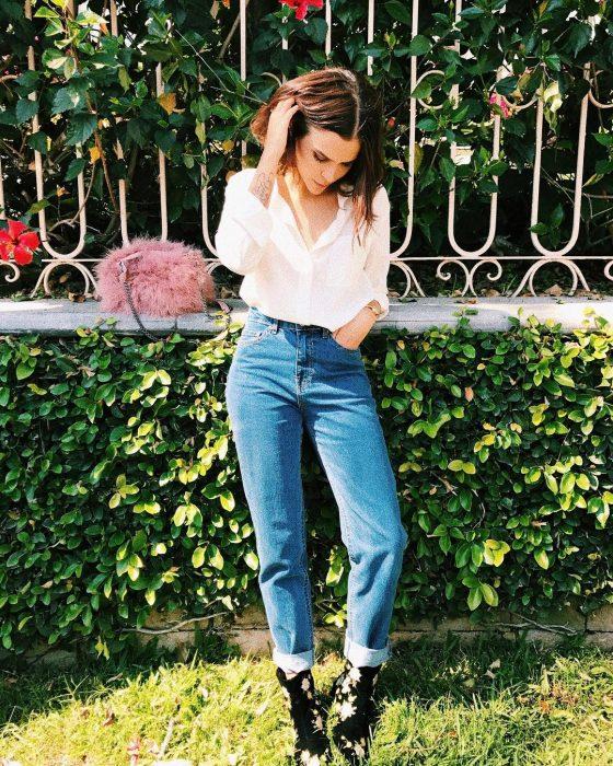 Yuya usando un pantalon de mezclilla y blusa blanca