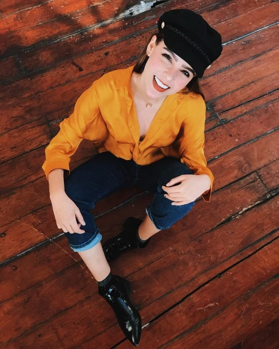 Yuya usando un pantalón de mezclilla blusa amarilla y gorra