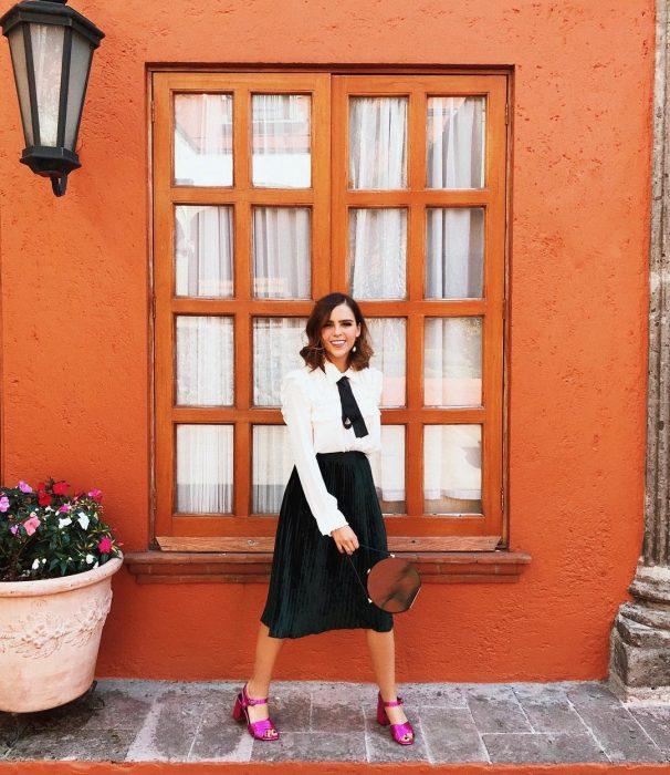 Yuya usando una falda negra y blusa blanca con zapatos rosas