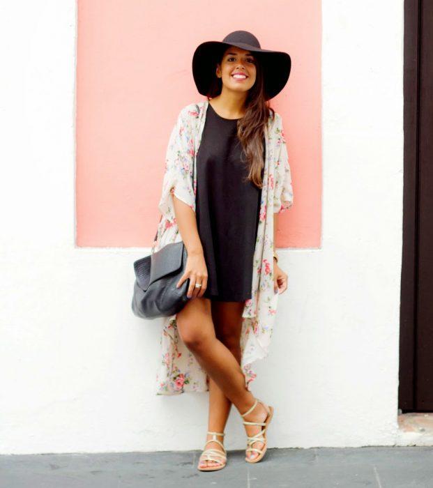 Chica usando un vestido negro con un kimono y un sombrero