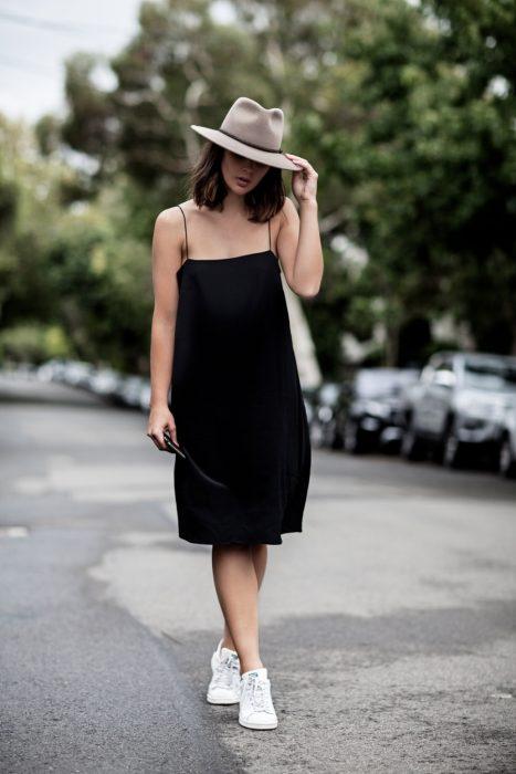 Chica usando un vestido negro con un sombrero de color café