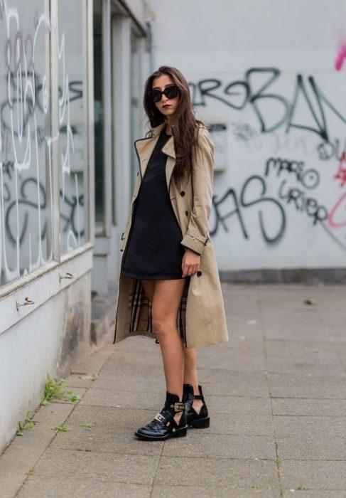 Chica usando un vestido negro con una gabardina de color café