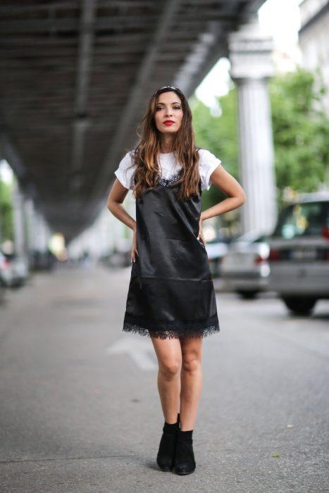 Chica usando un vestido negro con una blusa blanca abajo