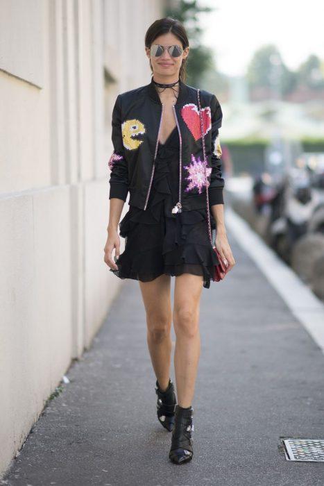 Chica usando un vestido negro con una bomber jacket y botines