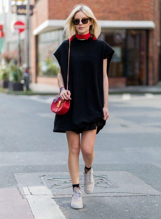 Chica usando un vestido negro con una mascada roja en el cuello