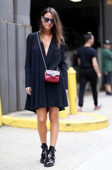 Chica usando un vestido negro con una bolsa de color roja