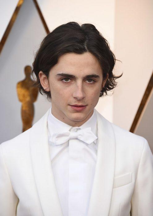 Timothée, chico usando traje blanco