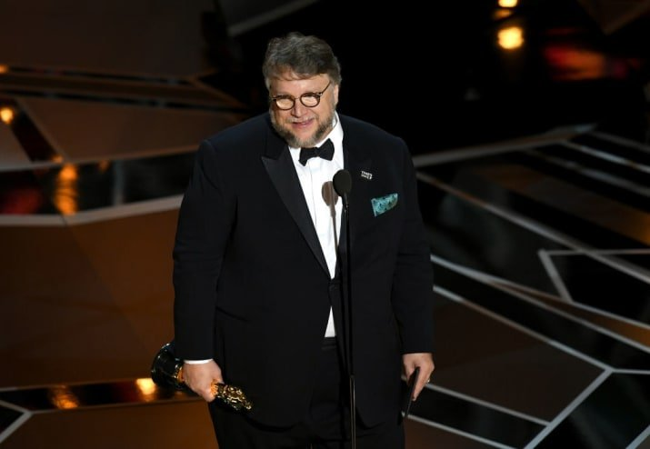 Guillermo del Toro recibiendo un Óscar, usando traje oscuro
