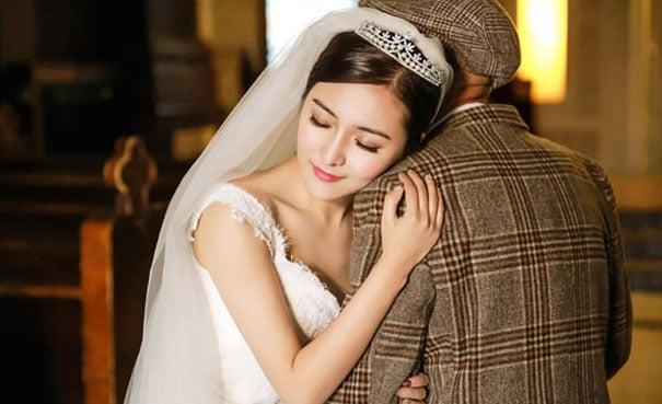Chica vestida de novia abrazando a su abuelo