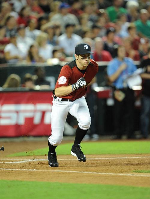 Nick Jonas corriendo mientras juega un partido de beisbol