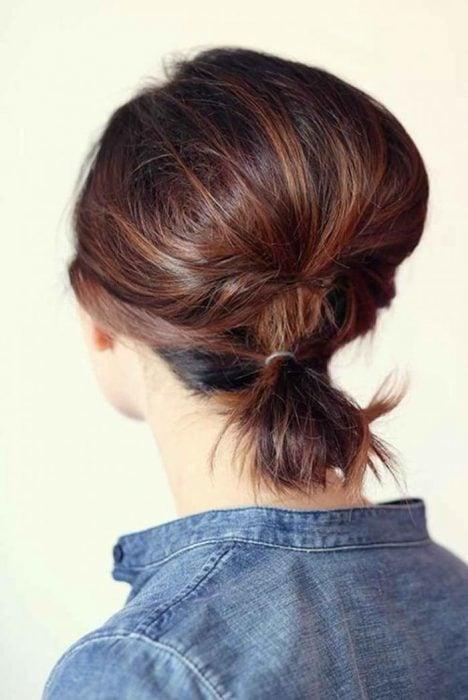 Chica con el cabello corto atado en una coleta baja