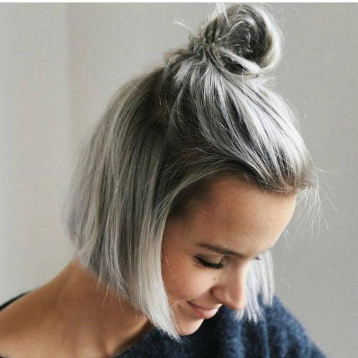 Chica con el cabello corto atado en un bun