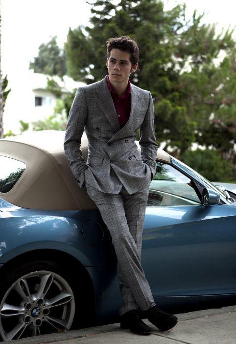 chico con traje sastre recargado en un auto