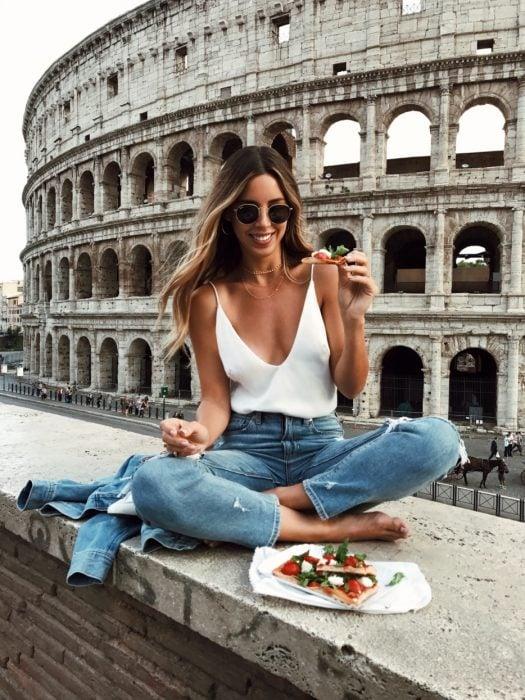 Chica sentada frente al coliseo romano mientras come
