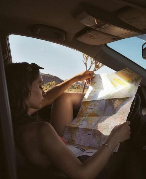 Chica sentada en un coche leyendo un mapa