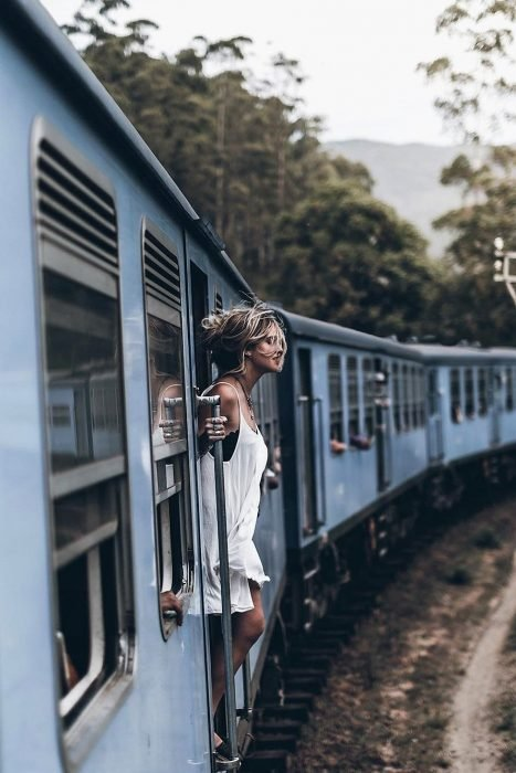 Chica asomando su cabeza mientras va viajando en tren