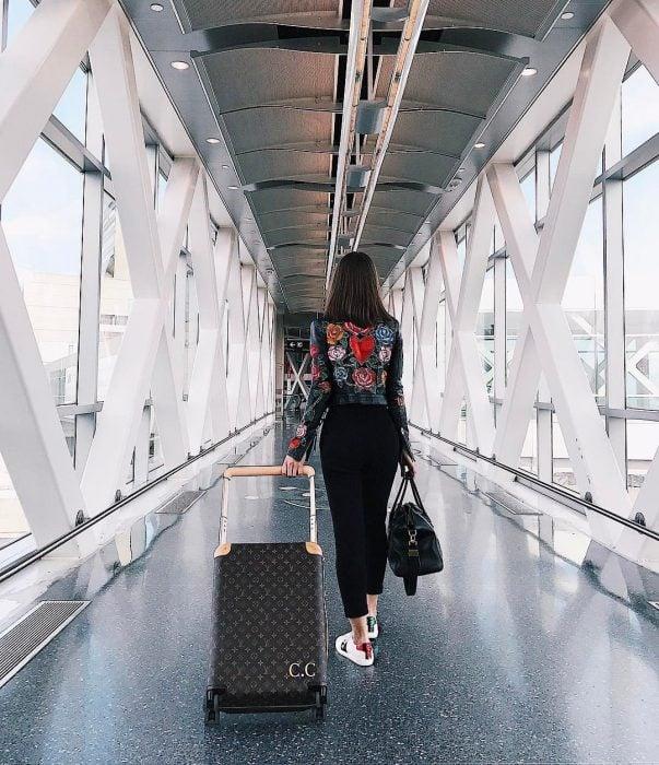 Chica caminando con su maleta mientras va en el aeropuerto
