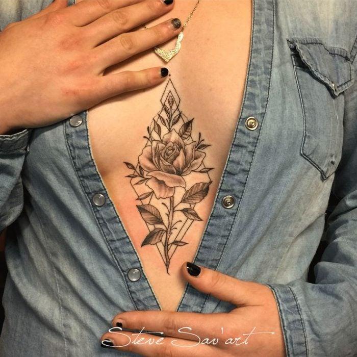 Chica con un tatuaje en medio de su escote
