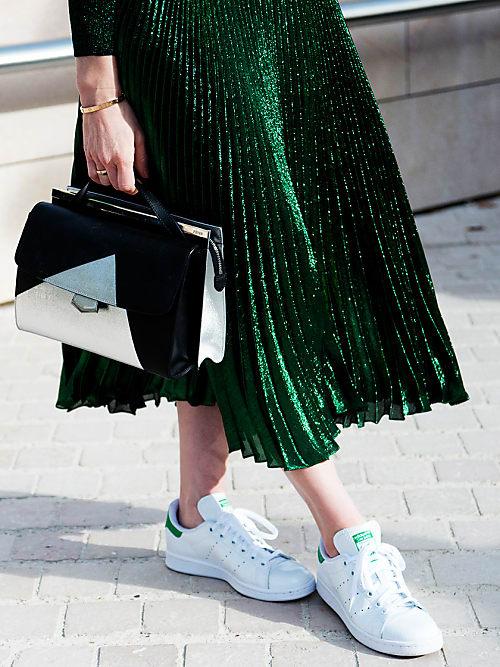 Chica usando una falda verde con unos tenis adedidas stan smith