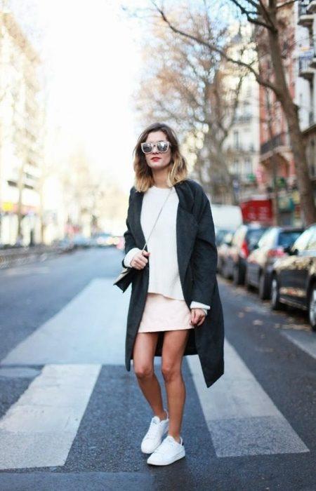 Chica usando una falda, tenis y saco