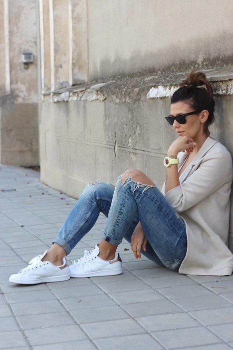 Chica sentada mientras está usando pantalones, saco y tenis