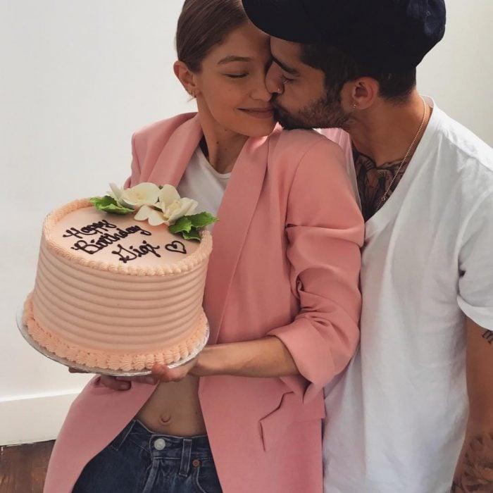 Gigi Hadid sosteniendo un pastel de cumpleaños mientras Zayn la besa