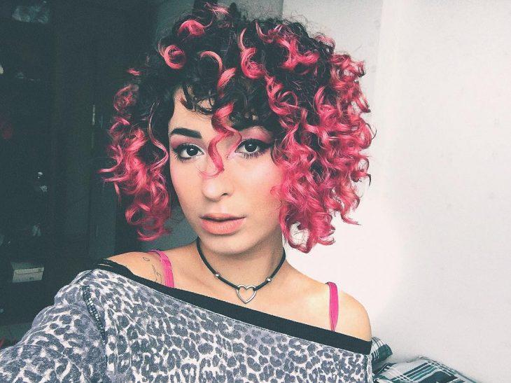 Chica con el cabello chino usando un tono rosa chicle
