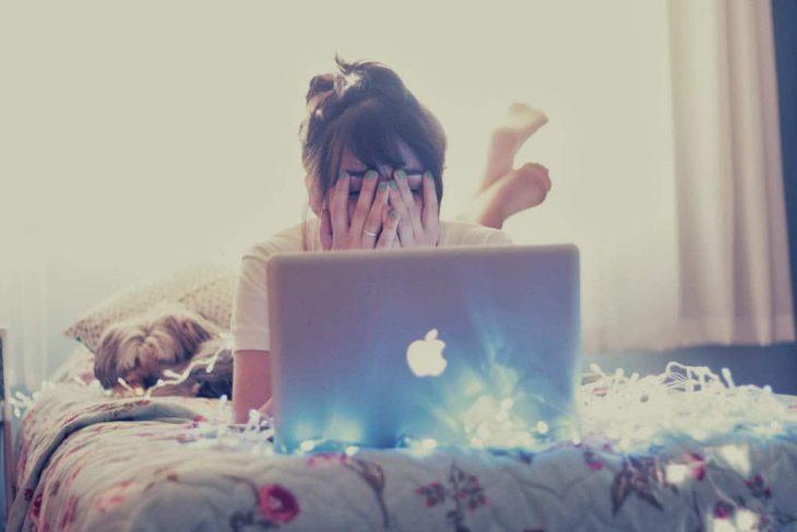 chica en su cama con su computadora