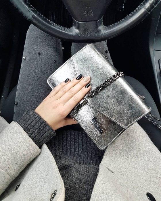 mujer mano y bolso metalico plata