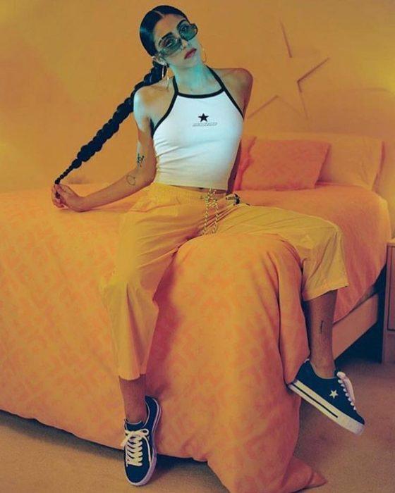 mujer en la cama naranja piernas abiertas