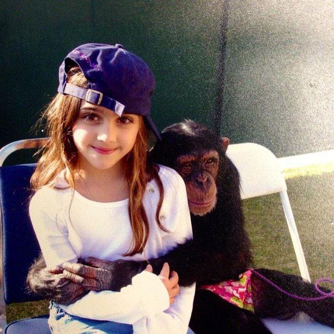 niña con gorra y chimpancé