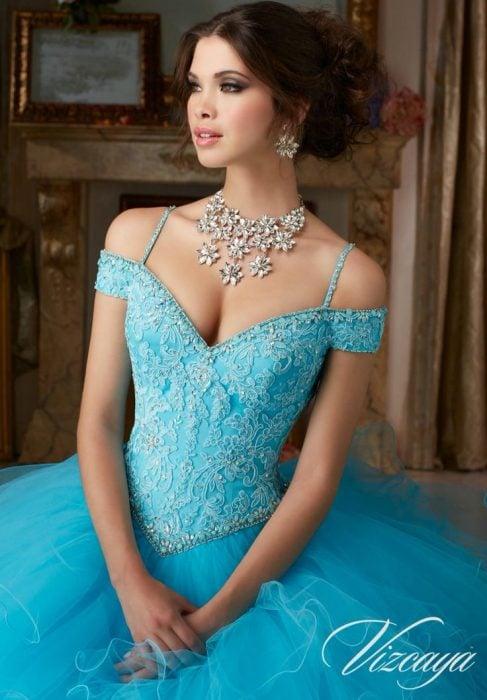 Chica usando un vestido de xv años color azul con tiara y collar de piedras brillantes