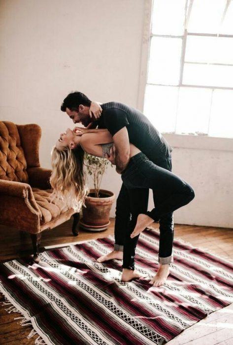 pareja de novios bailando en la sala de su casa