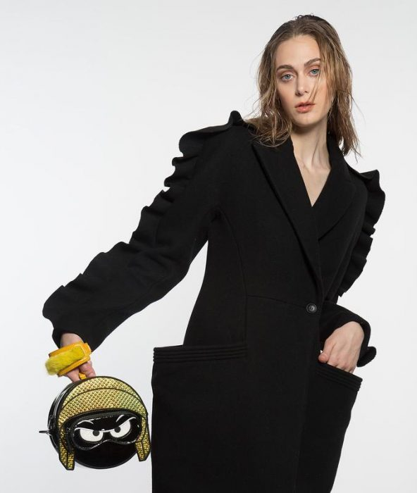 chica usando vestido negro con bolsas grandes