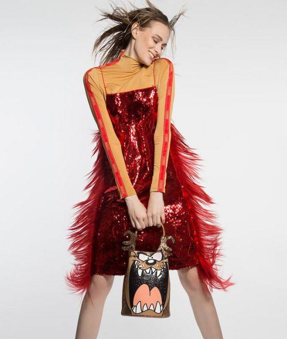 chica modelando un vestido rojo con plumas