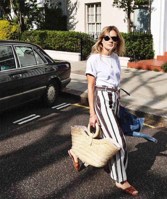 Chica usando un bolso straw handbags con un pantalón a rayas y blusa blanca