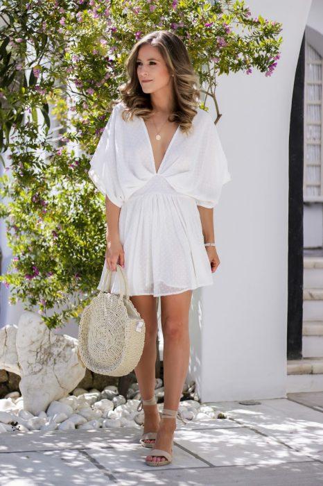 Chica usando un bolso straw handbags con un vestido blanco
