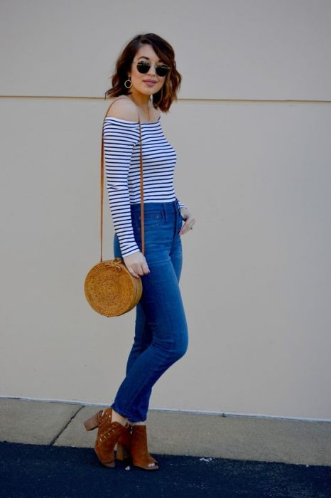 Chica usando un bolso straw handbags con jeans y blusa de rayas