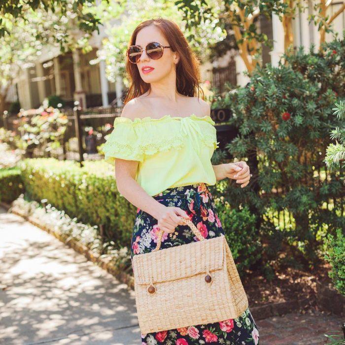 Chica usando un bolso straw handbags con falda de flores y blusa amailla