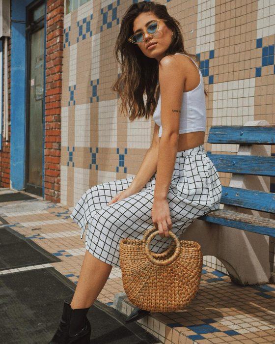 Chica usando un bolso straw handbags con un pantalón a cuadros y blusa blanca